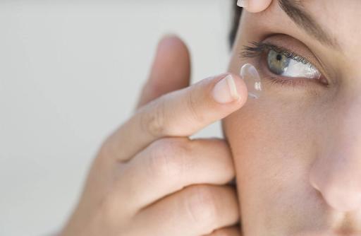 Une femme se posant une lentille sur l'oeil