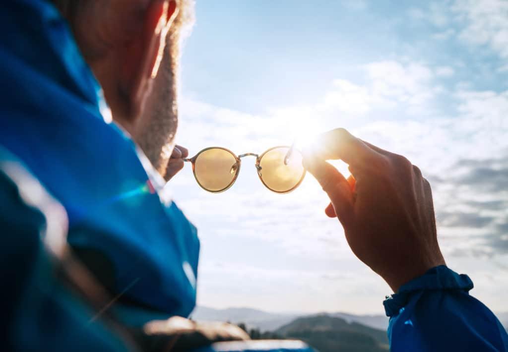Un homme tenant une paire de lunettes pour se protéger du soleil